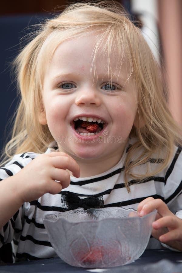 Ein kleines Mädchen, das Walderdbeeren isst stockbilder