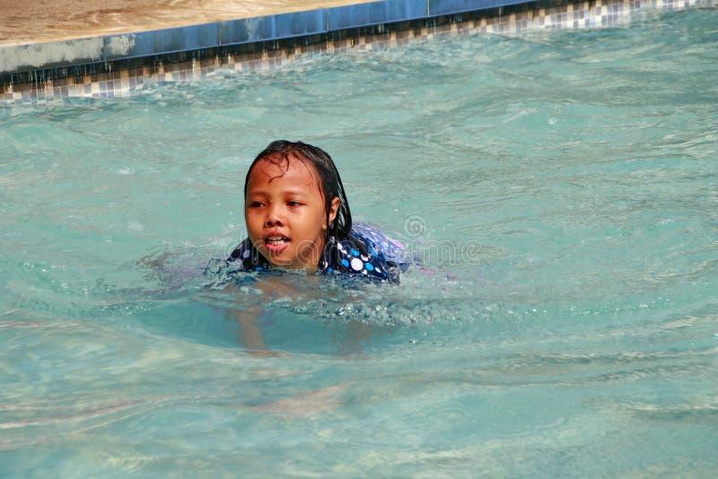 Ein kleines Mädchen, das Wasser im Pool spielt stockbild