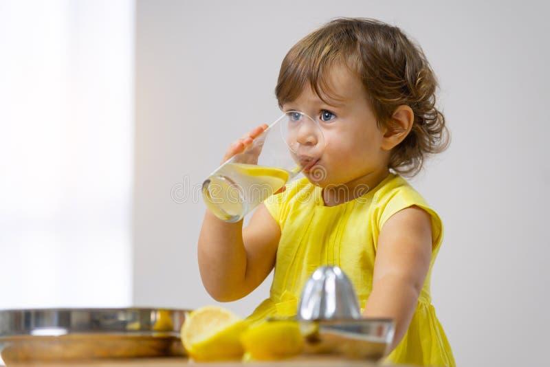 Ein kleines Mädchen in einem gelben Kleid schmeckt die gekochte Limonade stockfotografie