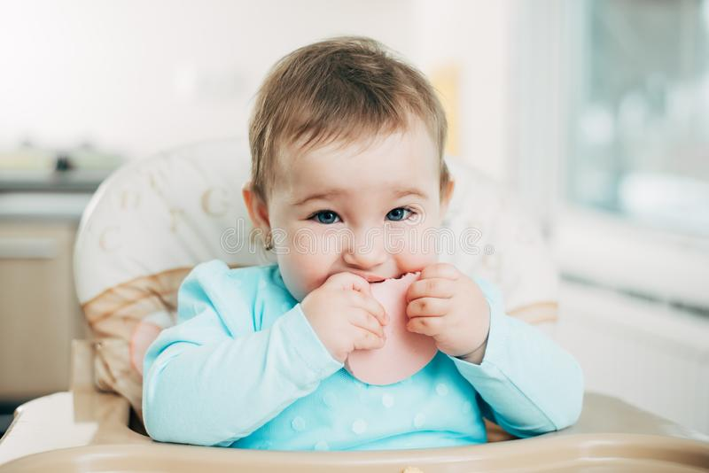 Ein kleines Mädchen in einem Hochstuhl, der ein Stück der gekochten Wurst isst stockbilder