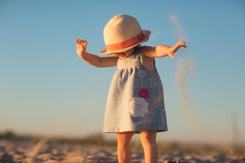 Ein kleines Mädchen in einem Hut gießt Sand auf dem Strand stockbilder