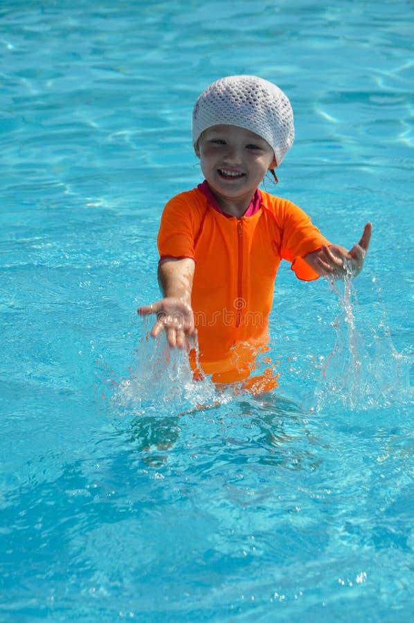 Ein kleines Mädchen in einem orange Badeanzug spritzt im Pool an einem sonnigen Tag lizenzfreie stockfotos
