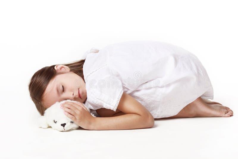 Ein kleines Mädchen in einem weißen Kleid, schläft eine Krüppel mit einem Lieblingsspielzeug vor weißem Hintergrund lizenzfreies stockbild