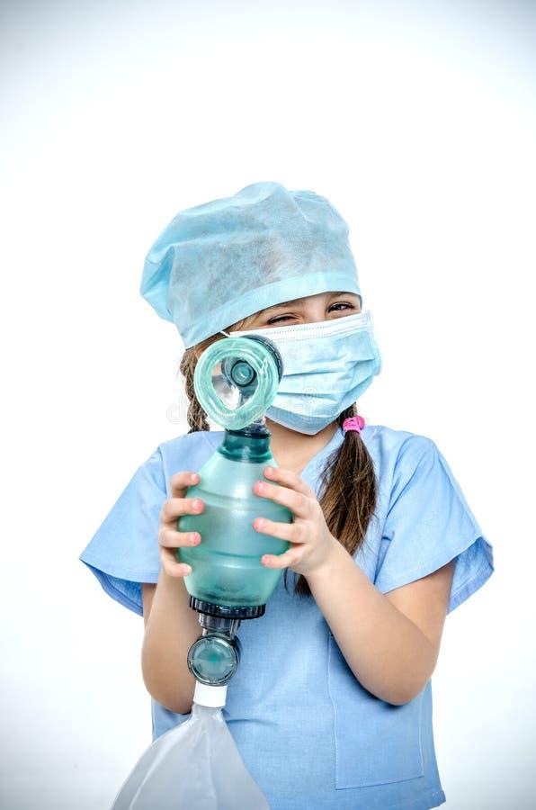 Ein kleines Mädchen in einer chirurgischen Klage hält ein ampu lizenzfreies stockbild