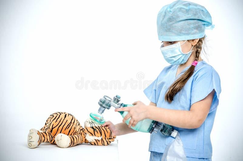 Ein kleines Mädchen in einer chirurgischen Klage macht ihrem Spielzeugtiger Maskenbelüftung stockfotos