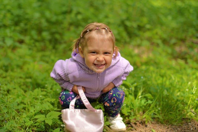 Ein kleines Mädchen in einer purpurroten Bluse mit einer Handtasche in ihren Händen macht Gesichter stockfotografie