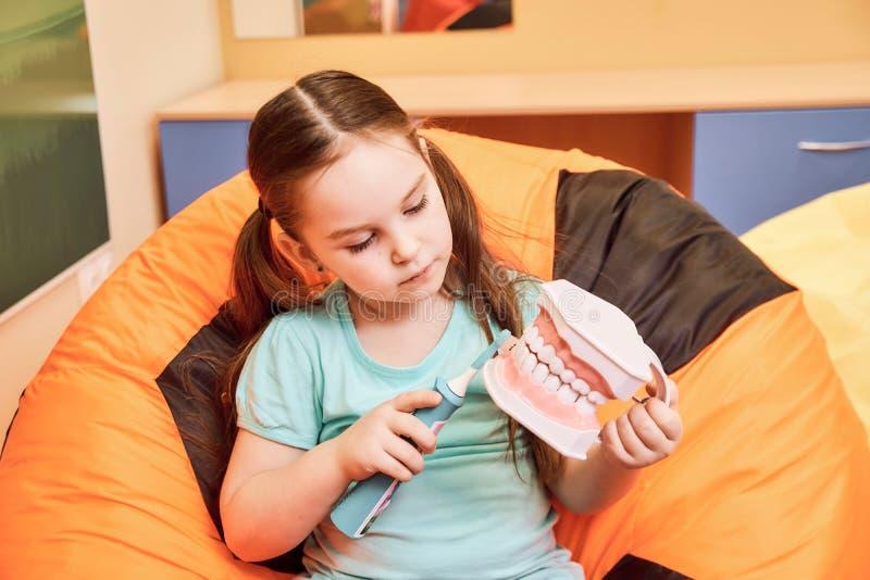 Ein kleines Mädchen in einer zahnmedizinischen Klinik, die eine zahnmedizinische Attrappe hält lizenzfreie stockfotos