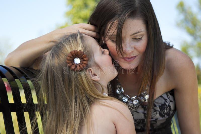 Ein kleines Mädchen erklärt ihrer Mamma ein Geheimnis lizenzfreie stockfotografie