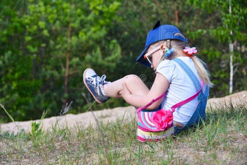 Ein kleines Mädchen fiel auf die Straße auf dem Gebiet, verkratzte ihr Knie und hält ihre Beine lizenzfreies stockfoto