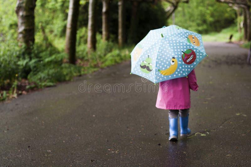 Ein kleines Mädchen geht an einem regnerischen Tag lizenzfreie stockfotos