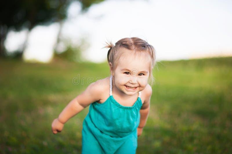Ein kleines Mädchen in grünes sarafan Lächeln im Sommer gegen einen Hintergrund des grünen jungen Grases lizenzfreies stockbild