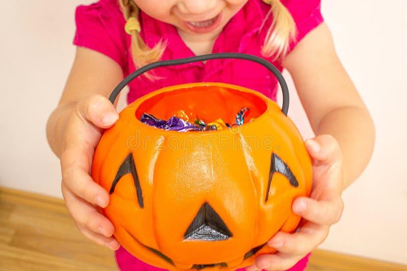Ein kleines Mädchen hält einen Kürbis mit Süßigkeit in ihren Händen und dehnt ihn aus, um sogar noch mehr Süßigkeiten für Hallowe stockbild