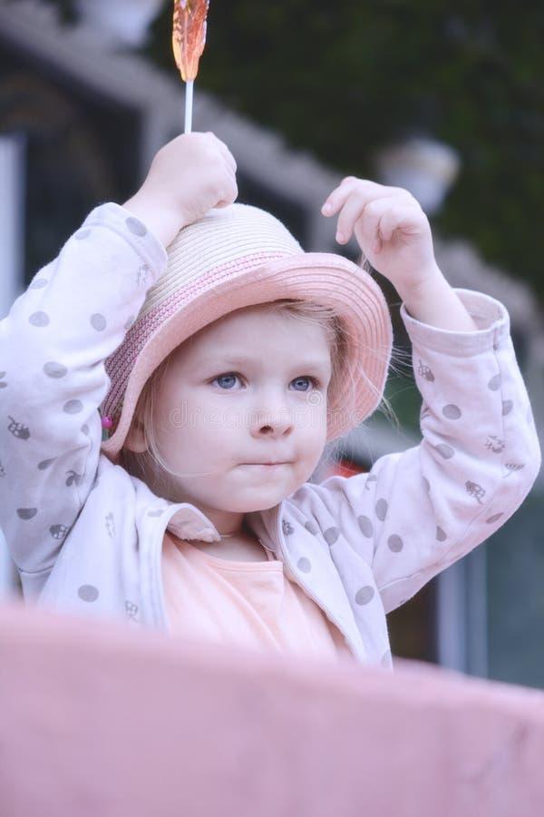 Ein kleines Mädchen hält einen Lutscher in ihr überreichen ihren Kopf Porträt eines schönen Kindes in einem Strohhut stockbild
