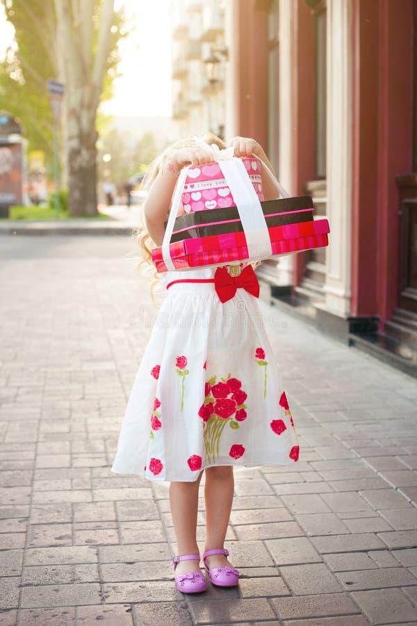 Ein kleines Mädchen hält Kästen mit Geschenken lizenzfreies stockfoto