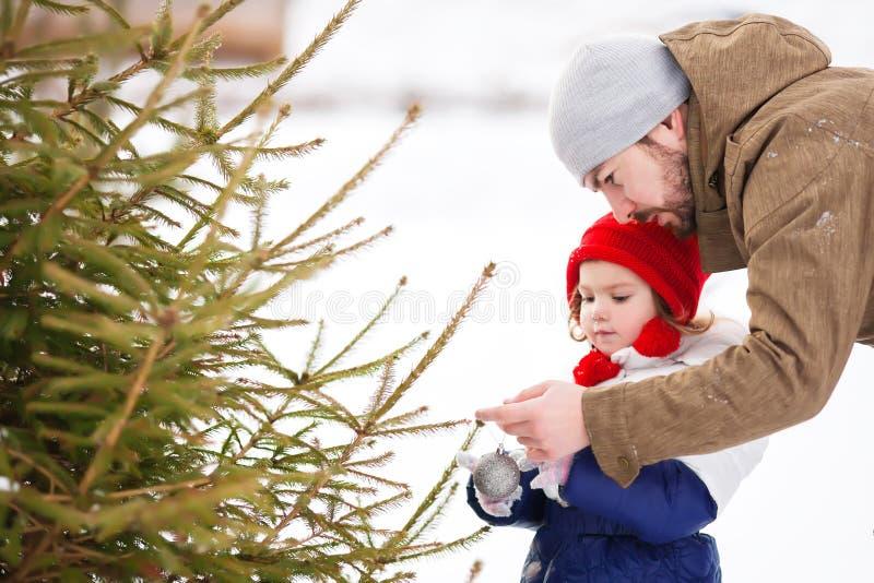 Ein kleines Mädchen hilft ihrem Vater, einen Weihnachtsbaum draußen zu verzieren stockfotos