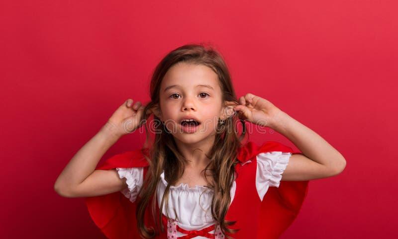 Ein kleines Mädchen im kleinen Rotkäppchenkostüm im Studio auf einem roten Hintergrund lizenzfreies stockfoto
