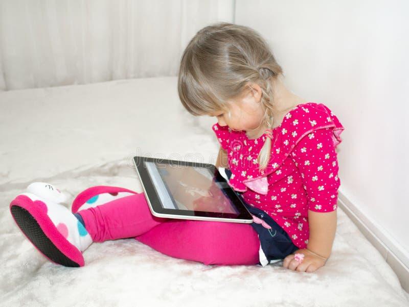 Ein kleines Mädchen ist, aufpassend sitzend und Karikaturen auf eine Tablette lizenzfreies stockfoto
