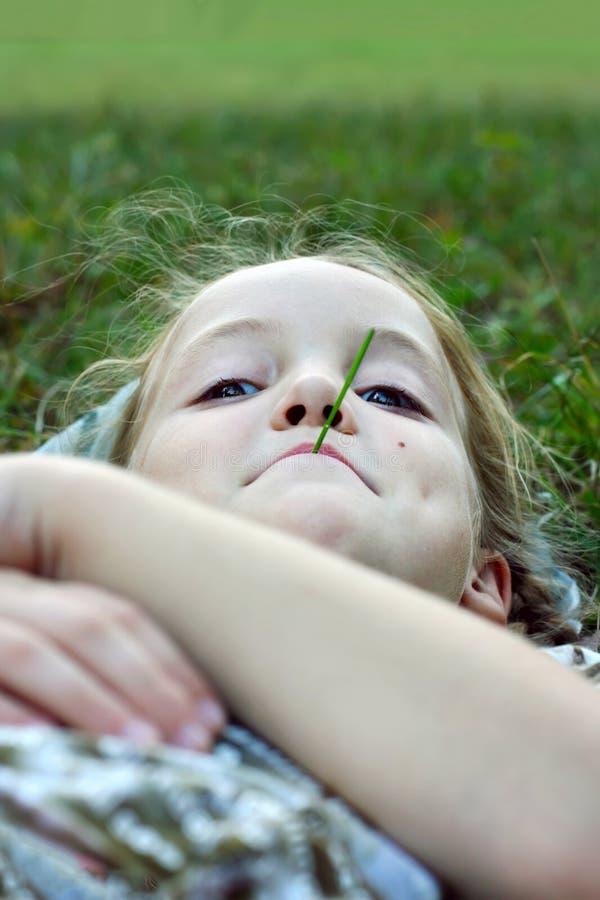 ein kleines Mädchen liegt auf dem Gras mit einem Grashalm in ihrem mou lizenzfreies stockbild