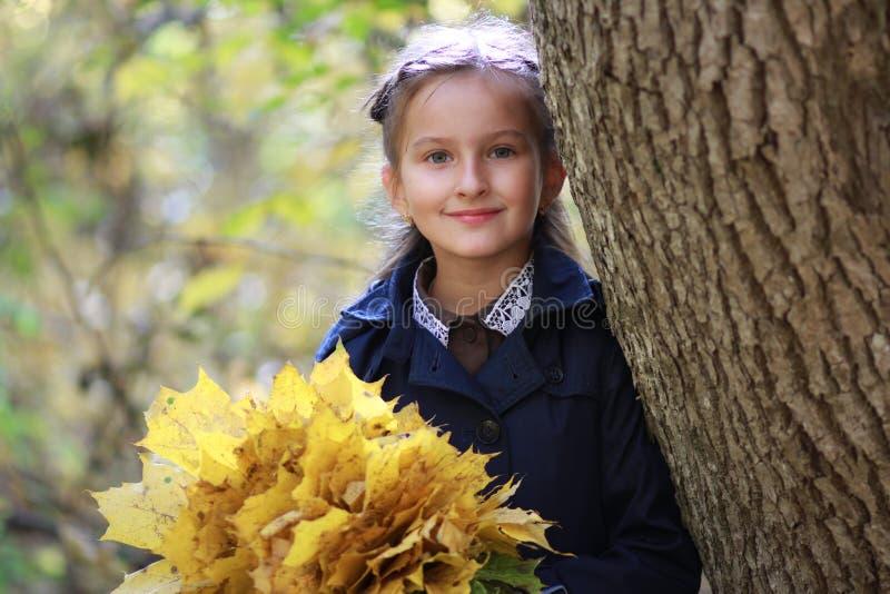 Ein kleines Mädchen mit einem Blumenstrauß von gelben Blättern in den Händen lizenzfreie stockfotografie