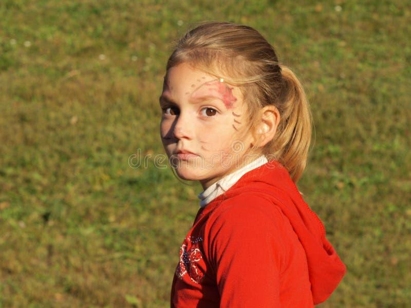 Ein kleines Mädchen mit einem Gesichtsmake-up und einem nachdenklichen Blick lizenzfreie stockfotos