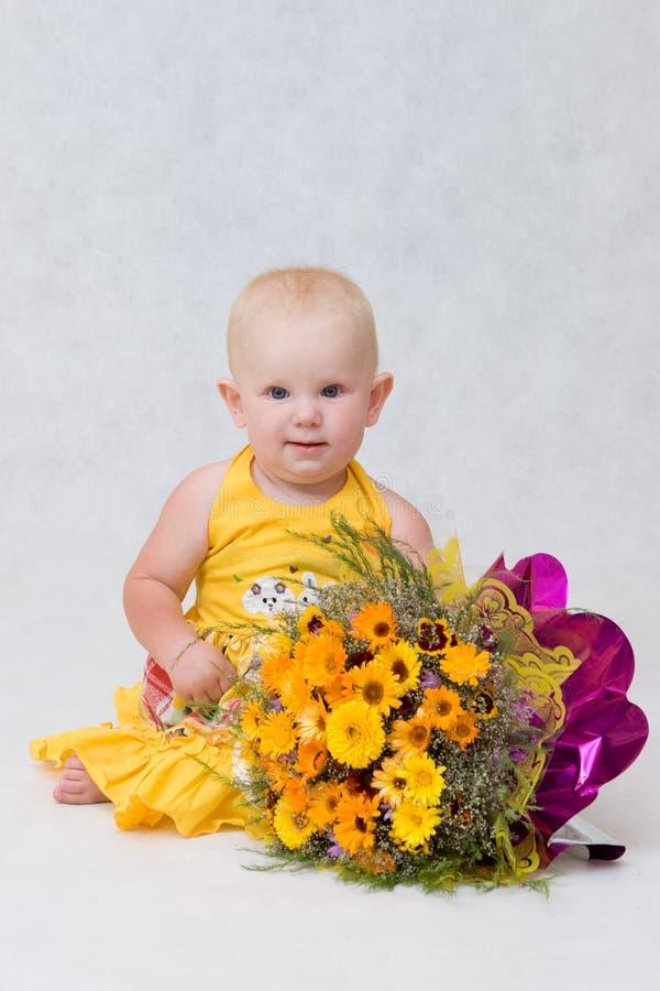 Ein kleines Mädchen mit einem großen Blumenblumenstrauß stockfotos