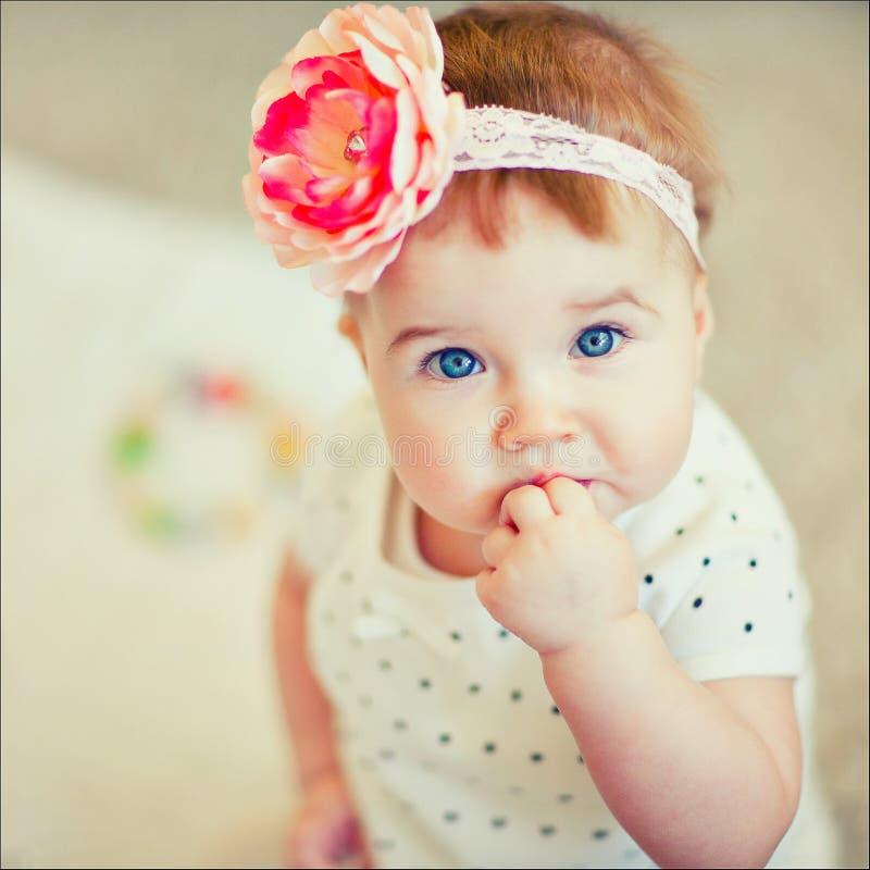 Ein kleines Mädchen mit einer Bogenblume auf dem Kopf lizenzfreies stockbild