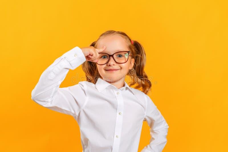 Ein kleines Mädchen mit einer Brille hält einen Finger am Kopf, eine Idee kam in einem Kind lizenzfreie stockfotos