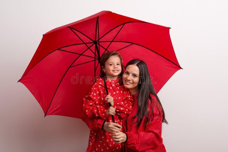 Ein kleines Mädchen mit ihrer Mutter unter einem Regenschirm auf einem weißen Hintergrund lizenzfreies stockfoto
