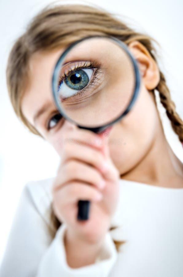 Ein kleines Mädchen mit Zöpfen hält eine Lupe vor ihrem Auge stockfoto