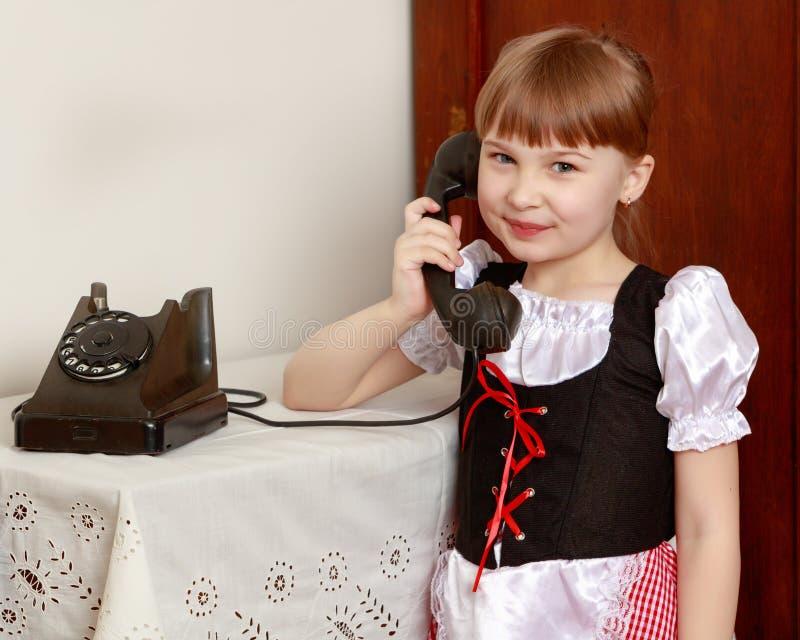 Ein kleines Mädchen schellt am alten Telefon lizenzfreies stockbild