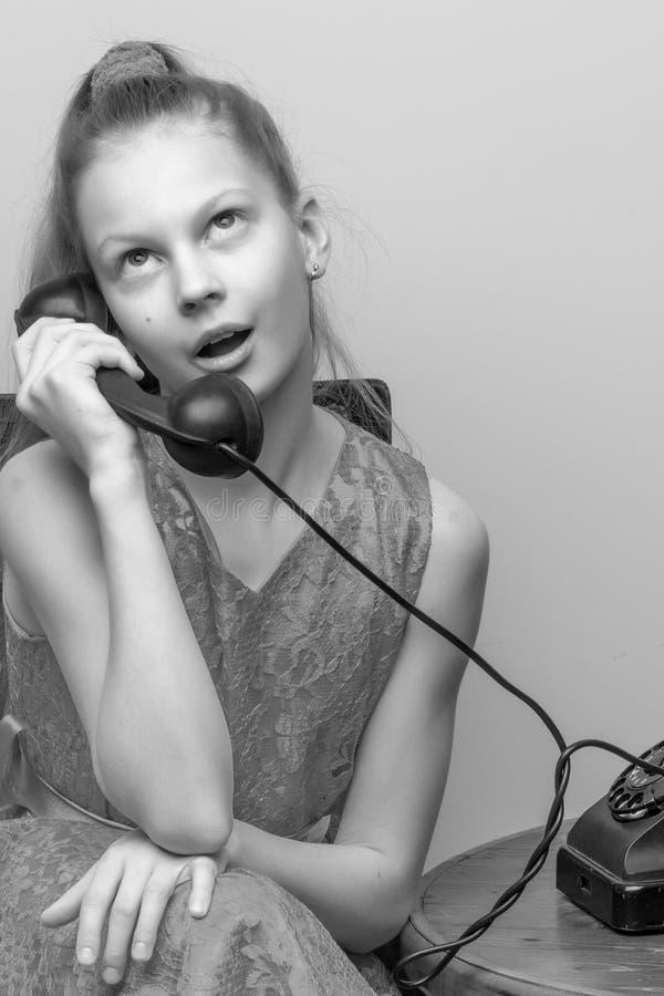 Ein kleines Mädchen schellt am alten Telefon stockbilder