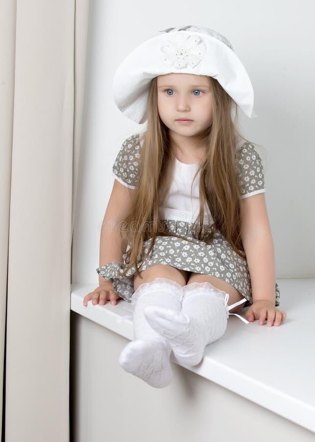 Ein kleines Mädchen sitzt am Fenster mit Jalousie lizenzfreies stockbild