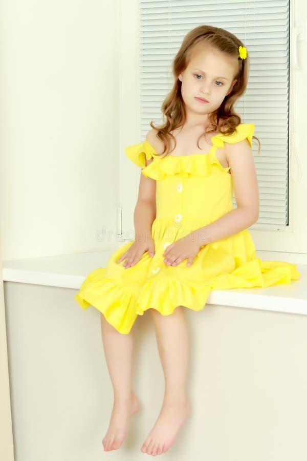 Ein kleines Mädchen sitzt am Fenster mit Jalousie stockfoto