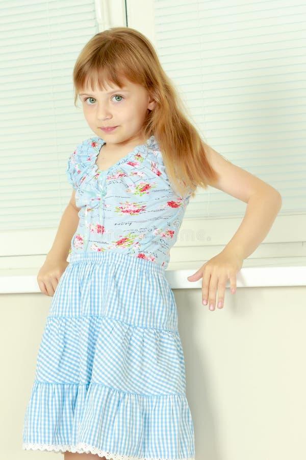 Ein kleines Mädchen sitzt am Fenster mit Jalousie lizenzfreie stockbilder