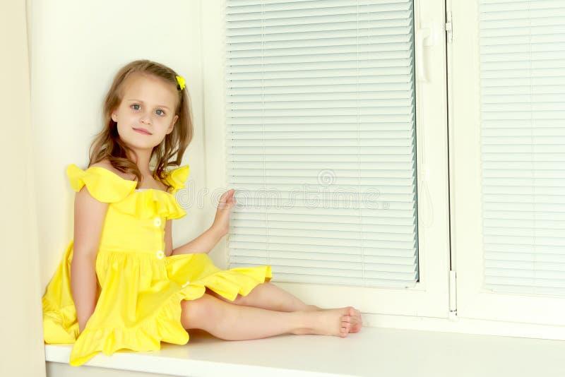 Ein kleines Mädchen sitzt am Fenster mit Jalousie lizenzfreie stockfotos