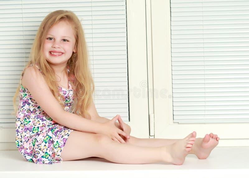 Ein kleines Mädchen sitzt am Fenster mit Jalousie lizenzfreies stockfoto