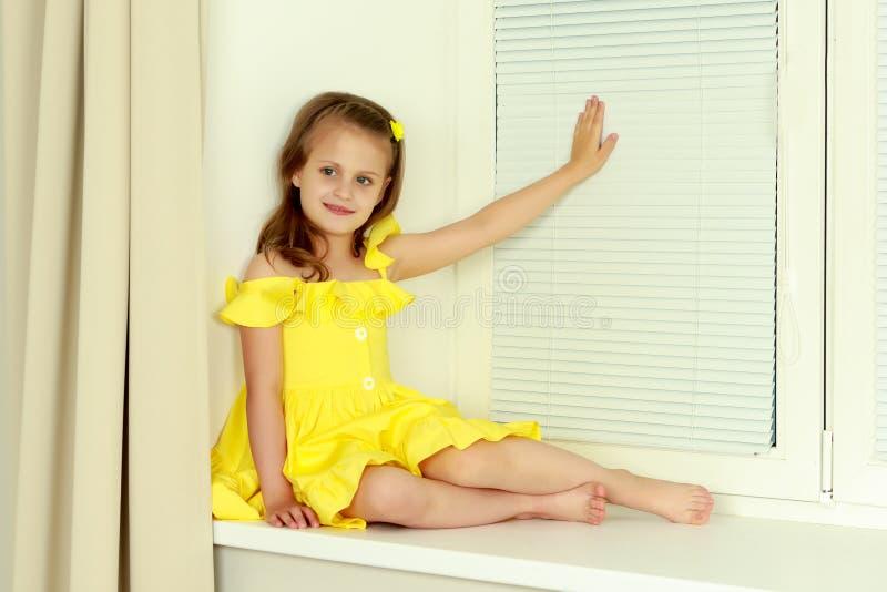 Ein kleines Mädchen sitzt am Fenster mit Jalousie stockfotos
