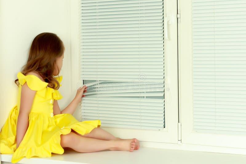 Ein kleines Mädchen sitzt am Fenster mit Jalousie stockbilder