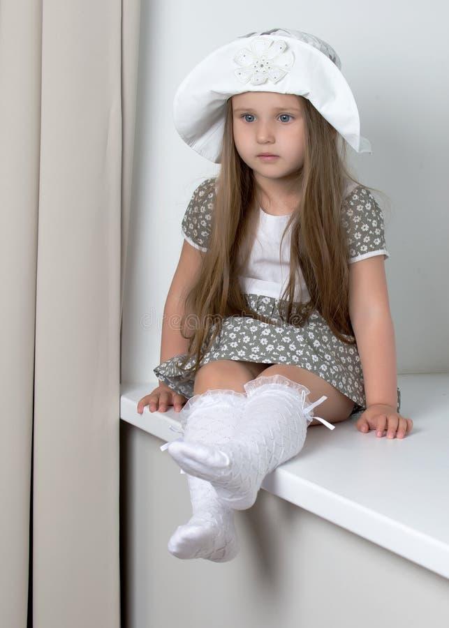 Ein kleines Mädchen sitzt am Fenster mit Jalousie stockfotografie