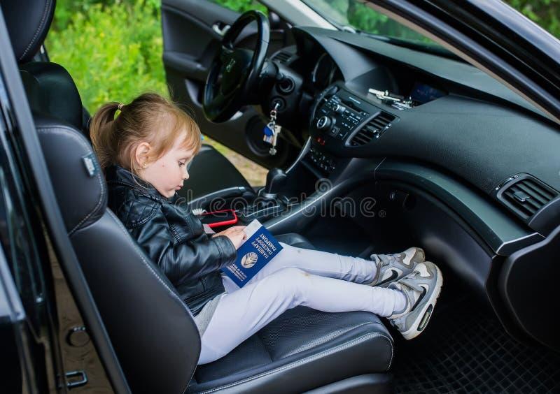 Ein kleines Mädchen sitzt im Autositz im Pass eines belarussischen Staatsbürgers stockbilder