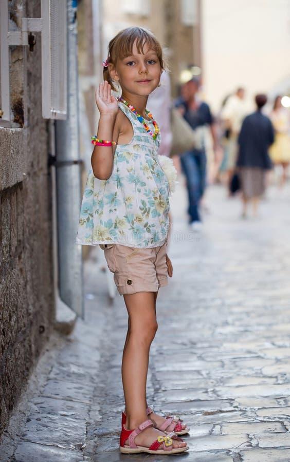 Ein kleines Mädchen steht auf der Abendstraße stockfotos