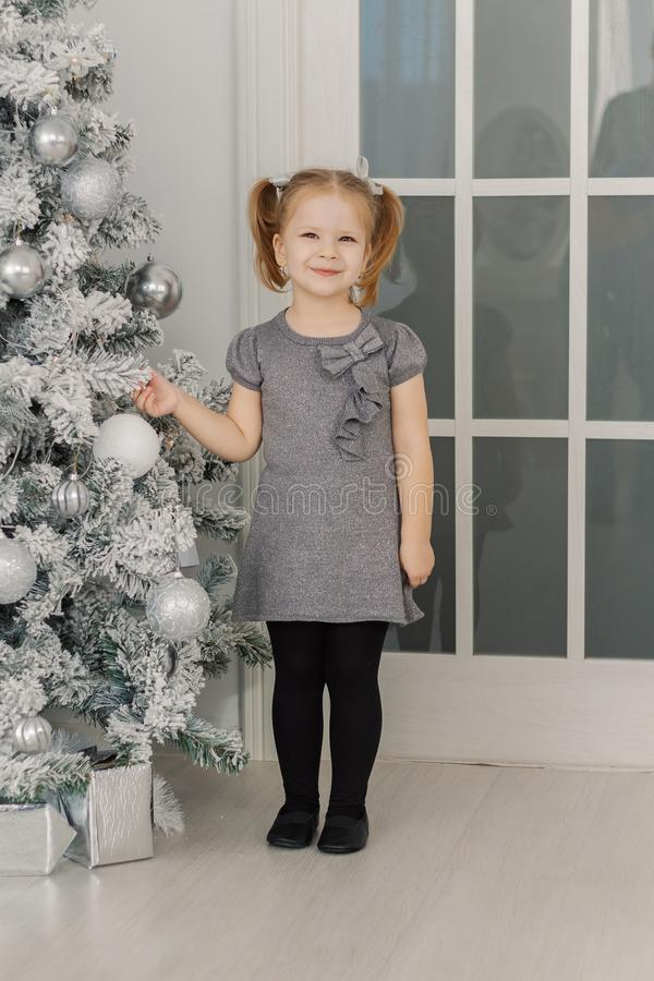 Ein kleines Mädchen steht einen Weihnachtsbaum bereit und berührt Spielwaren lizenzfreies stockbild