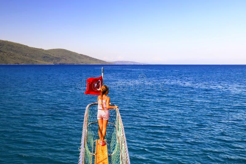Ein kleines Mädchen steht nahe der türkischen Flagge auf dem Bogen des Schiffs und segelt entlang das Ägäische Meer stockbild