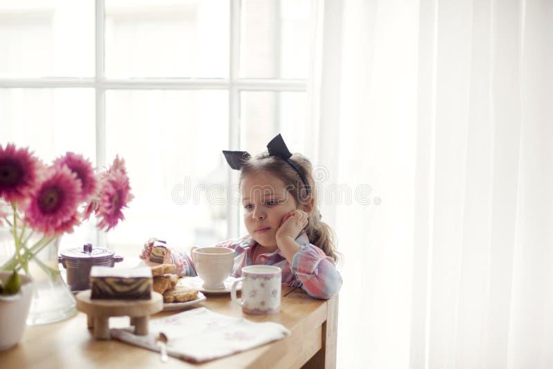 Ein kleines Mädchen am Tisch isst Frühstück am Fenster Guten Morgen Kopieren Sie Platz lizenzfreie stockfotografie
