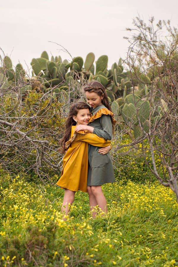 Ein kleines Mädchen umarmt ihre Schwester fest in einem Dickicht von den Niederlassungen und von Kakteen, die in altmodischer Kle stockfotos