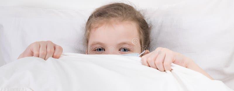 Ein kleines Mädchen versteckte sich im Bett in einer medizinischen Maske, um sich vor Infektion zu schützen lizenzfreie stockbilder