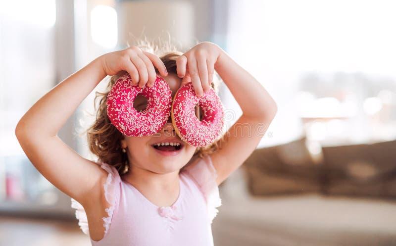 Ein kleines M?dchen mit Donuts zu Hause, Spa? habend lizenzfreie stockfotos