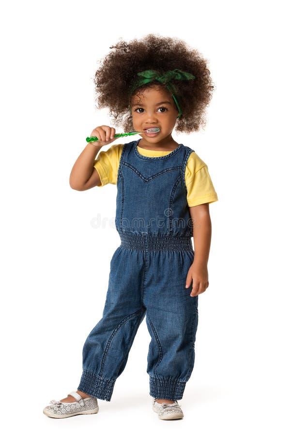 Ein kleines nettes Afroamerikanermädchen, das ihre Zähne, lokalisiert putzt lizenzfreie stockfotografie