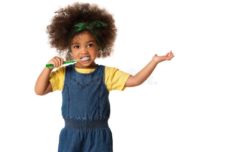 Ein kleines nettes Afroamerikanermädchen, das ihre Zähne, lokalisiert putzt lizenzfreie stockbilder