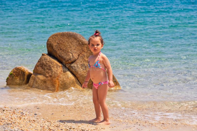 Ein kleines nettes Baby spielt auf einem Strand nahe dem Meer lizenzfreie stockfotos